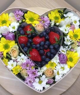 Композиция из цветов с клубникой и голубикой в коробке-сердце